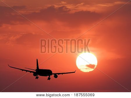 Silhouette of a airplane and colorful sky with sun. Landscape with passenger airplane is flying in the orange sky with clouds at sunset. Travel background. Passenger airliner. Business trip. Aircraft