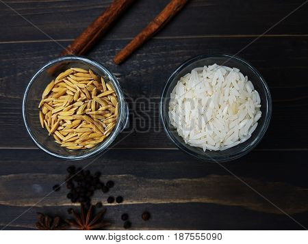 Rice and paddy in sepearated glasses on dark wooden table decorated with cinnamon sticks black pepper seeds and star anise