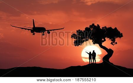 People under the crooked tree and airplane on the background of orange sky with sun. Silhouette of a couple on the hill tree passenger aircraft and colorful sky with clouds at sunset. Landscape