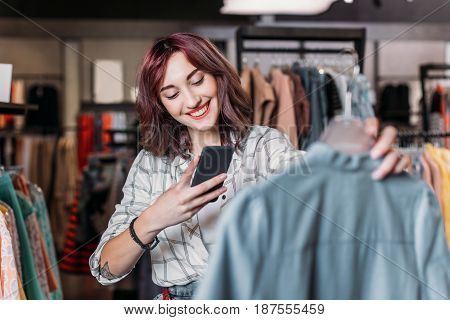 Young Hipster Girl Taking Photo Of Clothes In Boutique, Clothes Shopping Concept