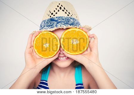 Llittle girl in swimsuit and summer hat having fun with half oranges making fake eyeglasses, toned image