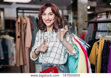Young Hipster Girl Smiling With Thumb Up In Boutique, Clothes Shopping Concept