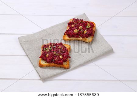 toasts with fresh beetroot spread on beige place mat