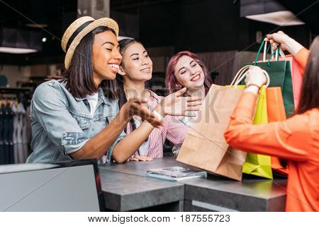 Happy Young Women Buying Clothes And Looking At Shopping Bags, Young Girls Shopping Concept