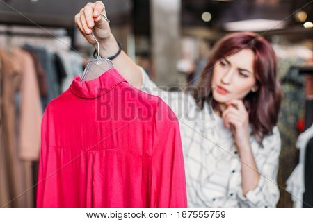 Young Pensive Hipster Girl Choosing Clothes In Shopping Mall, Boutique Shopping Concept