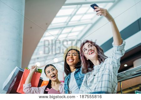 Low Angle View Of Smiling Young Women With Shopping Bags Taking Selfie, Young Girls Shopping Concept