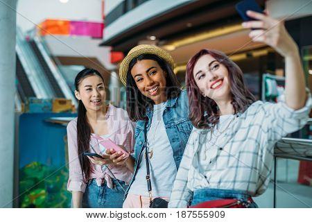 Smiling Young Women Taking Selfie In Shopping Mall, Young Girls Shopping Concept