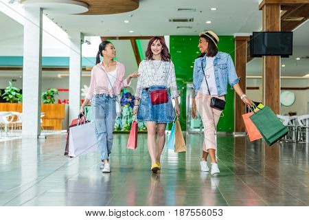 Happy Stylish Young Women Walking With Shopping Bags, Young Girls Shopping Concept