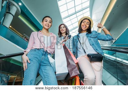 Low angle view of smiling young women with shopping bags on escalator in shopping mall young girls shopping concept