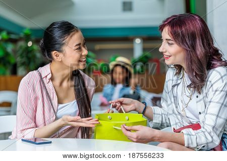 Smiling Young Women With Shopping Bag Sitting Together And Talking, Young Girls Shopping Concept