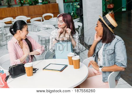 Smiling Young Women Sitting At Table With Paper Cups And Showing New Stylish Shoes, Young Girls Shop