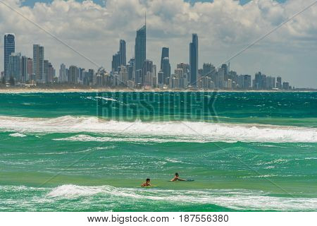 Gold Coast Australia - February 21 2016: Two young surfers on surfing boards in water with Gold Coast cityscape skyline on the background