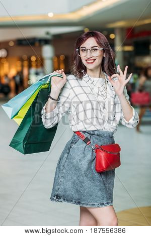 Happy Young Woman With Shopping Bags Showing Ok Sign, Boutique Shopping Concept