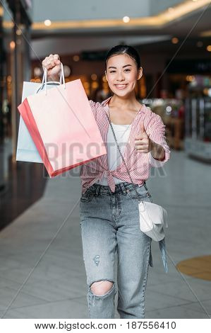 Happy Stylish Woman With Shopping Bags Showing Thumb Up In Mall