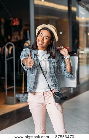 Portrait Of Happy Stylish Woman With Shopping Bags Showing Thumb Up In Mall