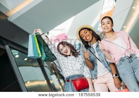 Portrait Of Smiling Women With Shopping Bags Showing Thumbs Up At Shopping Mall