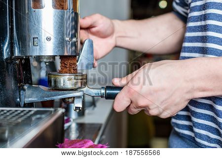 Side View Of Barista Cleaning Coffee Machine In Cafe