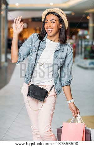 Happy Stylish Woman With Shopping Bags Showing Ok Sign In Mall