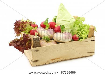 mix of cabbage, lettuce and turnips in a wooden crate on a white background