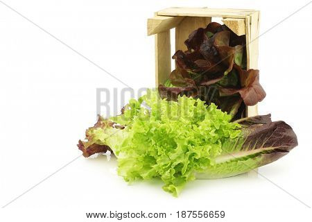 fresh romaine and red lettuce in a wooden crate on a white background