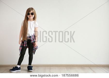 Cute little girl on light wall background. Fashion concept