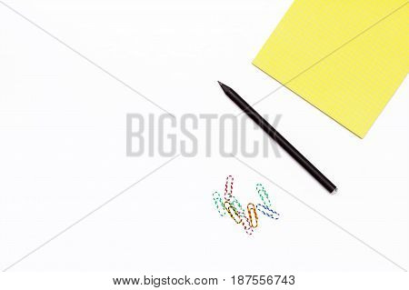 Black Pencil, Colored Paper Clips And A Yellow Notepad. Minimal Concept Desktop In The Office.