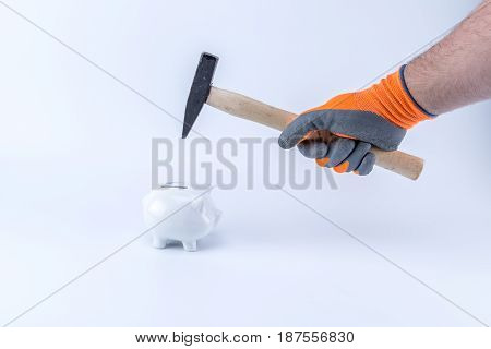 Caucasian Hand Wearing Gray Orange Gloves Holding A Hammer Trying To Break A Piggy Saving Bank Money