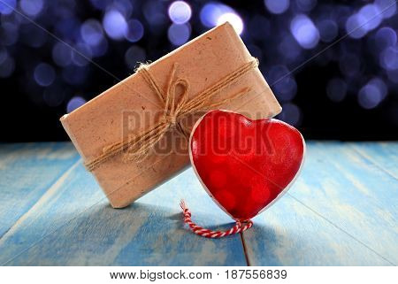 red heart and gift on blue wooden boards on the background of sparkles