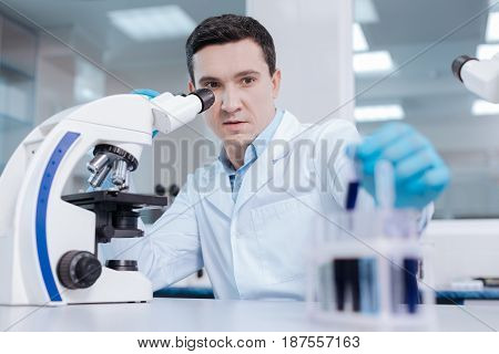 Do not be so serious. Handsome lab assistant sitting in front of microscope touching ocular while looking aside