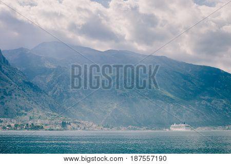 cruise ship sailing in beautiful bay with mountains. Kotor Bay Montenegro.