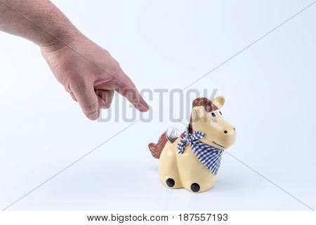 Caucasian Hand Pointing A Country Horse Piggy Saving Bank Moneybox With A Coin On Its Back Hole