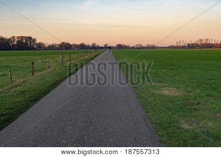 One Cyclist On Rural Road At Sunset.