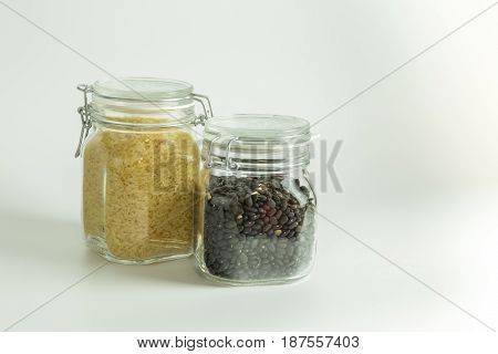 Rice And Beans Dry And Raw In Glass Jars Isolated On White Background