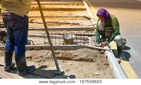 KUALA LUMPUR MALAYSIA - MAR 22 2017: Unidentified worker working digs a hole with a shovel and spade in the sand at road construction site. in Kualum Lumpure Malaysia.