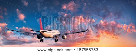 Airplane. Landscape with big white passenger airplane is flying in the blue sky with red and orange clouds at colorful sunset. Travel. Passenger airliner. Business trip. Commercial plane. Aircraft