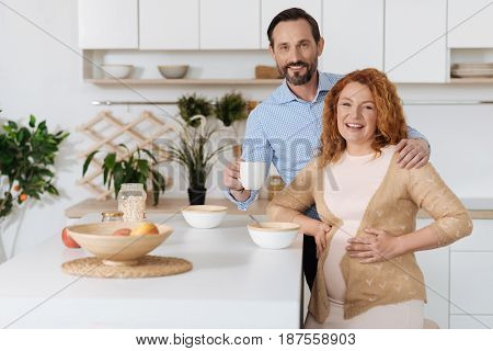 Expecting husband embracing his riant pregnant wife while both posing and looking at camera in the kitchen.