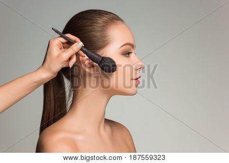 Beautiful female eyes with make-up and brush on white