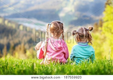 Two sisters sitting on the grass and look at the mountains. The concept of travel lifestyle and family.