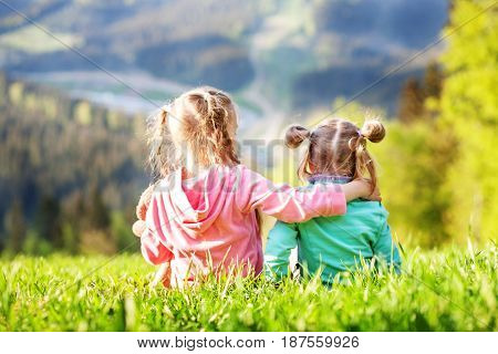 Two little sisters sitting on the grass and look at the mountains. The concept of travel lifestyle and family.