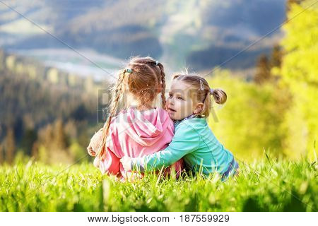 The little girl hugs her sister. The top of the mountain. The concept of travel lifestyle and family.