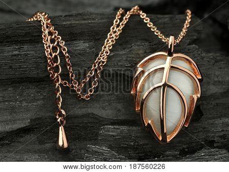 Gold jewelry pendant on dark coal background