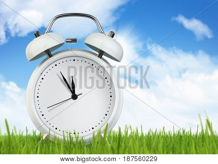 Blank alarm clock on grass with sky