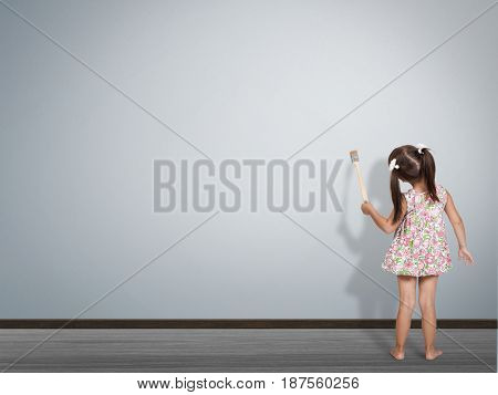 kid write with paint brush on blank wall back view