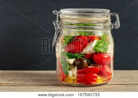 Mixed caprese salad in a closed lid glass mason jar on a wooden table with dark gray background