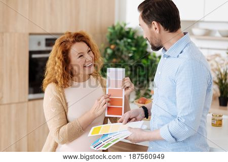 Do you like this one. Radiant pregnant woman showing a peach colour on a palette to her husband while discussing a nursery renovation.