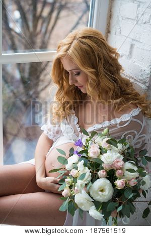 Beautiful pregnant girl smiling sitting on window with bouquet of flowers