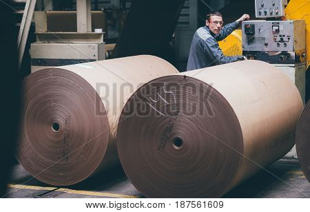 Paper mill factory worker operating equipment near paper rolls