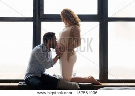 Tender sentiment. Mature expectant mother standing on her knees on a pillow and watching her husband kissing a pregnant belly.