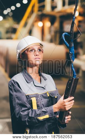 woman operating crane at paper mill factory