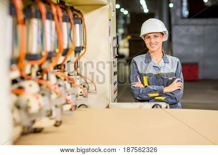 worker watching machine producing carton at a paper mill factory